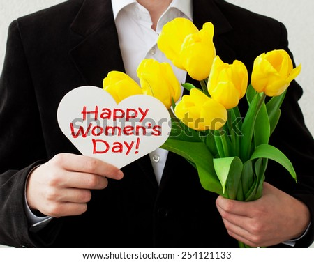 Happy Women's Day! man with a greeting card and yellow tulips - stock photo