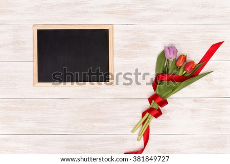 Happy Women's Day with tulips. Happy Women's Day on blackboard with tulips. White wooden table, top view on workplace. Tulips over shabby white table. - stock photo