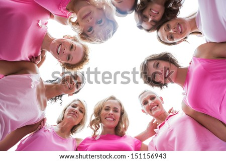 Happy women smiling in circle wearing pink for breast cancer on white background - stock photo