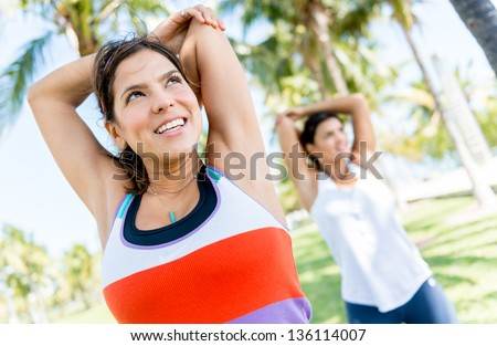 Happy women stretching arms before working out - stock photo