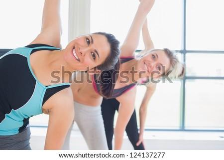 Happy women stretching in fitness studio of gym - stock photo
