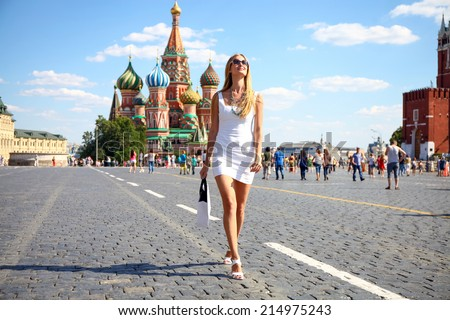 Happy women walking in white dress at the red square in Moscow - stock photo