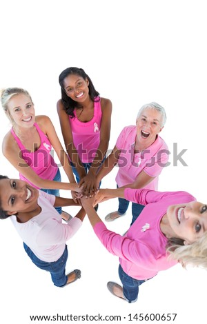Happy women wearing pink and ribbons for breast cancer putting hands together looking up at camera on white background - stock photo