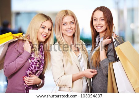 Happy women with shopping bags in store - stock photo