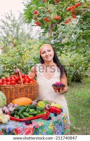 happy women with vegetables in garden - stock photo