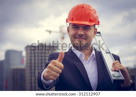 Happy worker architect showing success thumb up on the background of construction   - stock photo