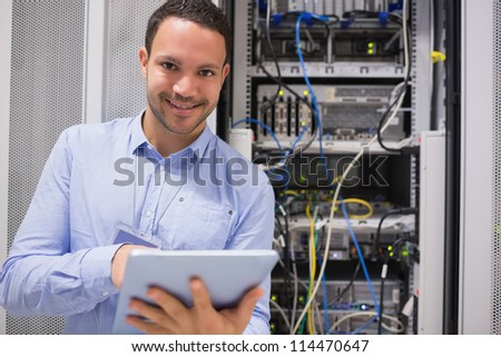 Happy worker with tablet pc in data centre - stock photo