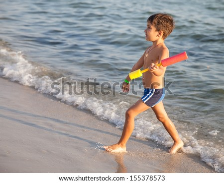 happy 5 year old child playing on the beach - stock photo