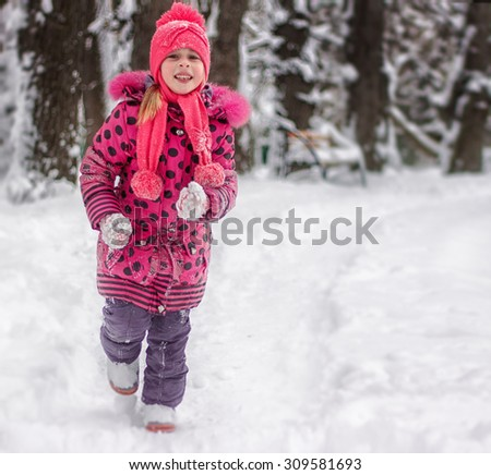Happy 5 year old girl running on snow-covered park - stock photo