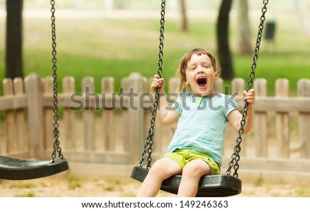 Happy 3 years baby on swing  in urban  park - stock photo