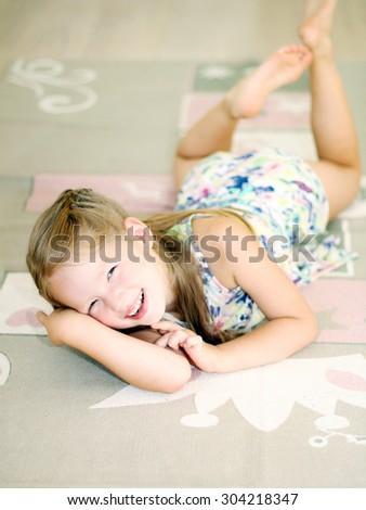 Happy 5 years girl lying on the carpet - stock photo