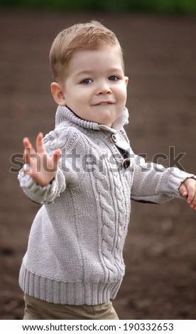 happy 2 years old baby boy in motion, running in a park - stock photo