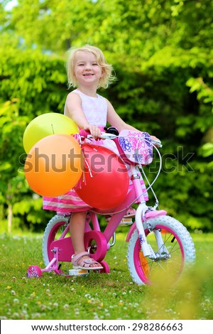 Happy 3 years old girl riding first bike. Adorable healthy preschool child biking outdoors on sunny summer day. Birthday gift idea for toddlers. - stock photo
