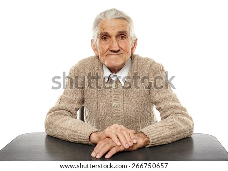 Happy 80 years old man sitting at the desk, studio shot - stock photo