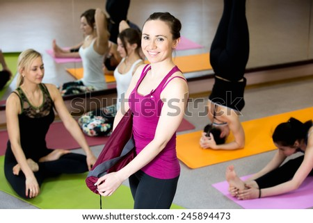 Happy yogi girl holding folded pink yoga mat, her class partners practice various asanas on the background - stock photo