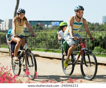 Happy young active family of four cycling on street road in summer day - stock photo