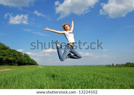 Happy young active girl jumping high because of happiness at the summer nature background - stock photo