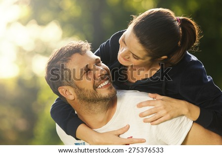 Happy young adult couple outdoors smiling, she holding on his back - stock photo