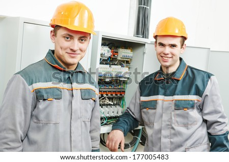 Happy young adult electrician builder engineer workers in front of fuseboard - stock photo