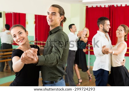 Happy young adults  enjoying of classical dance in class - stock photo