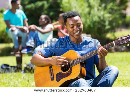 happy young african american college boy playing guitar on campus - stock photo