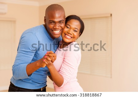 happy young african american couple dancing in their new house - stock photo