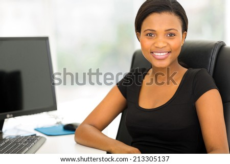 happy young african businesswoman relaxing in office - stock photo