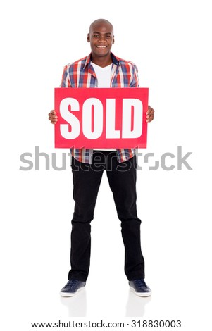 happy young african man holding a sold sign against white background - stock photo