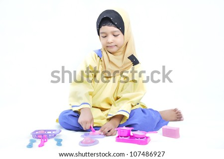 Happy, young and cute Muslim girl playing with a miniature cooking utensil toy in white isolated background. - stock photo