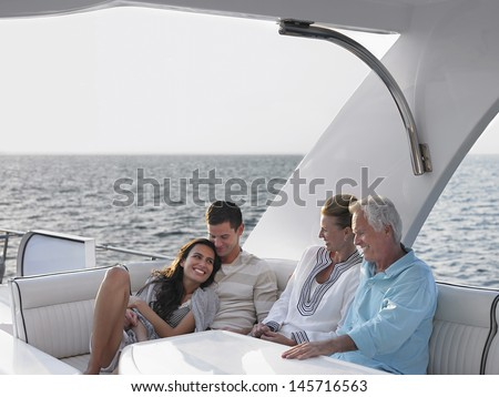 Happy young and middle aged couples relaxing on yacht - stock photo