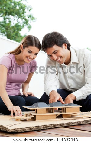 Happy young architects working on a wooden model house together - stock photo