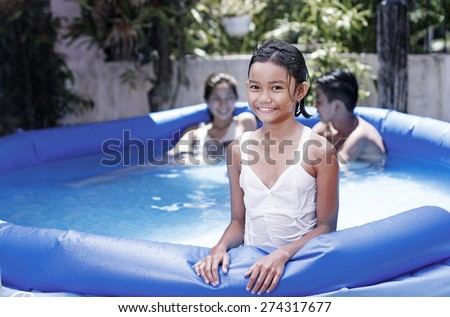 Happy young asian girl enjoying an outdoor summer bath on an inflatable swimming pool. - stock photo