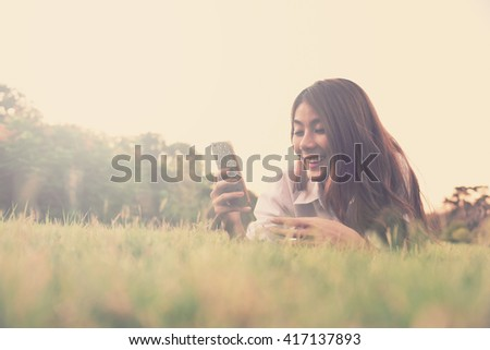 happy young asian woman hold cell phone on grass - vintage style with color paster tone - stock photo