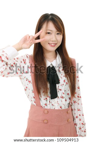 Happy young asian woman showing the peace sign - stock photo