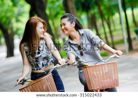 Happy young asian woman with bicycle in park - stock photo
