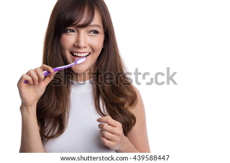 Happy young asian woman with healthy teeth holding a tooth brush - stock photo