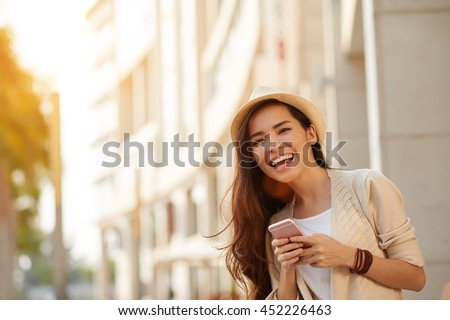 Happy young Asian woman with smartphone standing in the street - stock photo