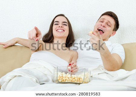 Happy young attractive couple sitting on the couch in living room at home covered with blanket and watch fanny comedy on television with popcorn. Cute woman and man watching cheerful and fun movie - stock photo