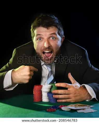 happy young attractive man grabbing poker chips pointing himself with his finger after winning bet gambling on table with playing cards on green felt at Casino - stock photo
