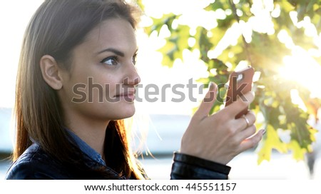 happy young attractive women using smart phone device networking with social media app. female person outdoors at sunset - stock photo