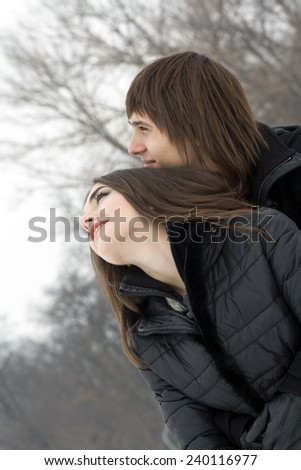 Happy young beautiful couple embracing and having fun in winter park. - stock photo