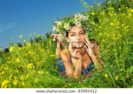 Happy young beautiful girl lying in flowers - stock photo