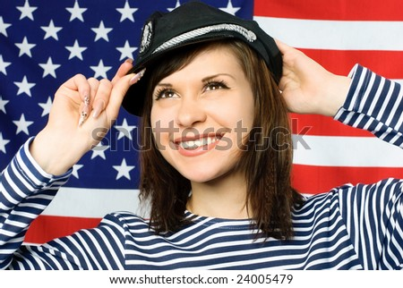 happy young beautiful sailor standing near the American flag - stock photo