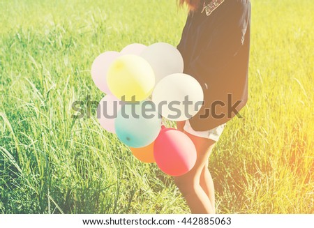 Happy young beautiful woman and colorful balloons in grassland. - stock photo