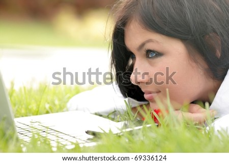 Happy young beautiful woman lying on the grass with laptop and red flower. Sunny day. - stock photo