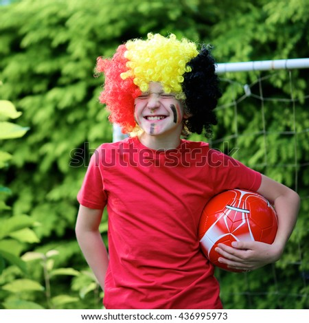 Happy young belgian boy having fun supporting Red Devils team during european football championship EURO 2016. Kid in Belgian national tricolour with painted flag on his face playing soccer outdoors. - stock photo