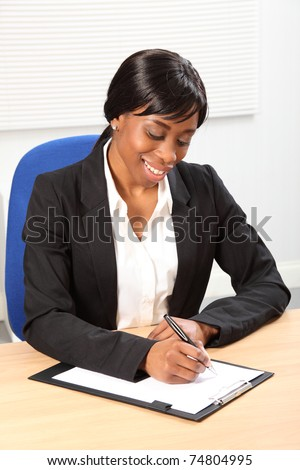 Happy young black woman working in office sitting to her desk signing a document. Picture taken from high angle. - stock photo