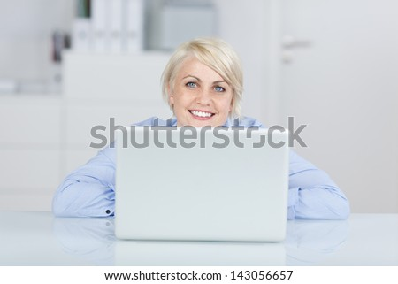Happy young blond businesswoman looking up in front of a laptop at office desk - stock photo