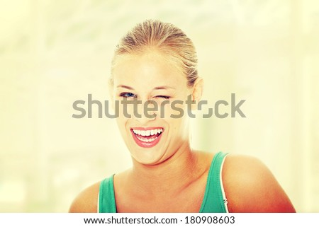 Happy young blond woman blinking.  - stock photo