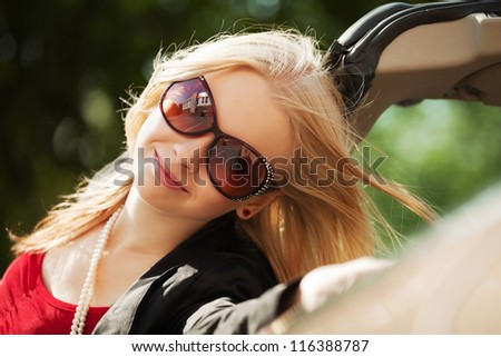 Happy young blond woman with a convertible car - stock photo